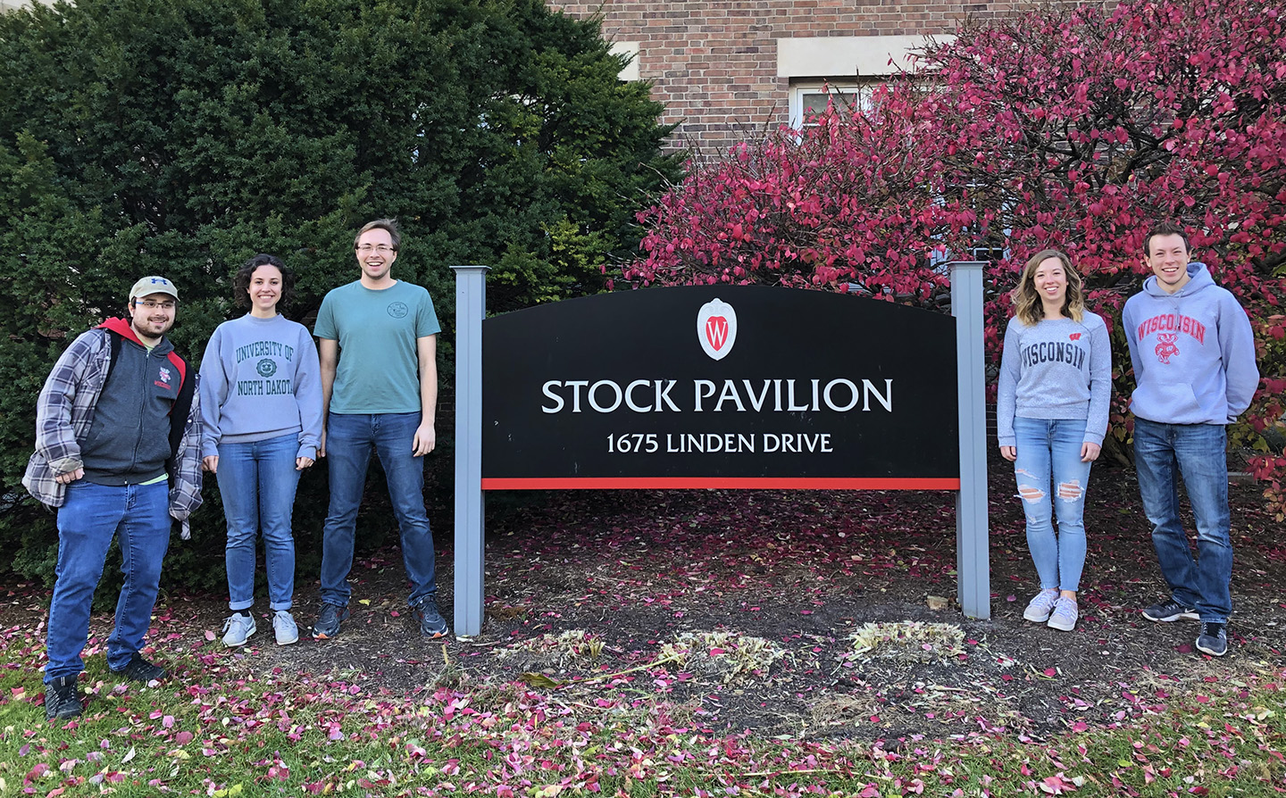 Five students standing next to the UW Stock Pavilion sign.